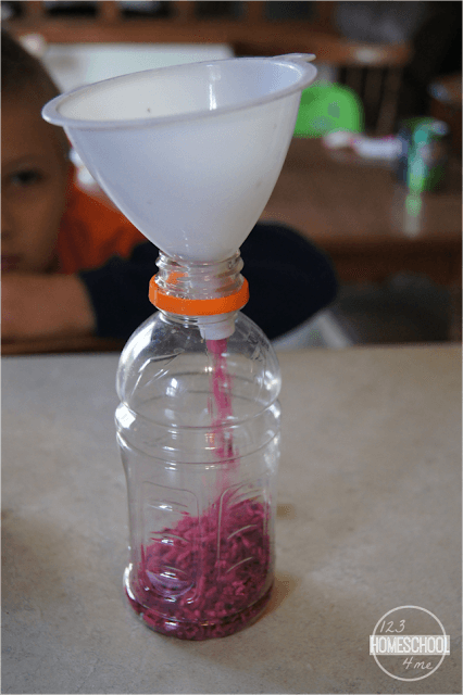 put-dyed-rice-in-recycled-plastic-bottle-using-a-funnel