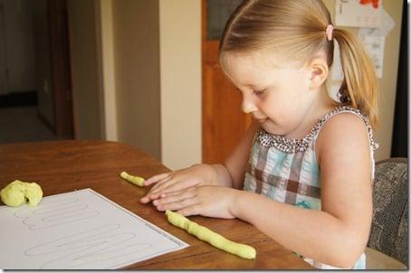 Preschooler using playdough mats