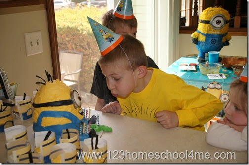 blowing out the minion birthday cake