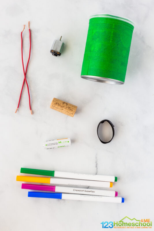 Small motor 1.5 -3 V thick elastic band 2 in x ½ in, AA Battery Pringles can or other small container cork 2 leads Paper Felt tip pens painters tape