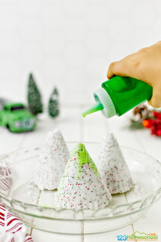 Pour a mixture of green food coloring and vinegar slowly onto the frozen trees to turn the trees green and melt the Christmas trees in this baking soda and vinegar science project for kids