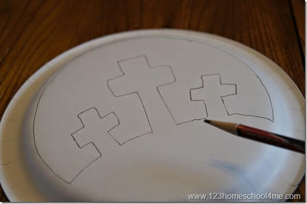 trace crosses on calvary scene on black paper plate