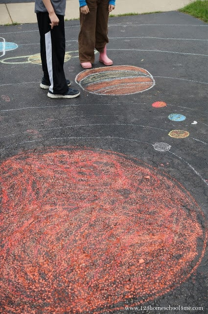 EPIC solar system project for kids that is easy to make by drawing the milk way galaxy, sun, planets, moon, asteroid belt and more with chalk on the driveway. Cute game idea for memorization too!