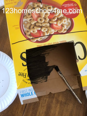 STEM Christmas project using cereal box, paint, batteries, electrical tape, and broken string of Christmas lights