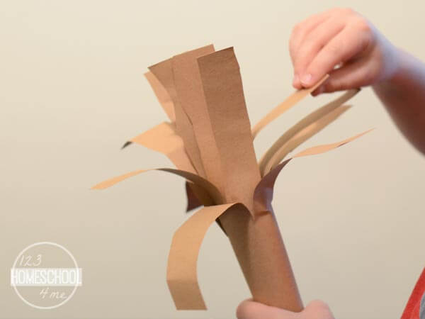 pull down the slits of construction paper to make branches