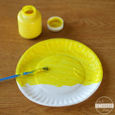 using yellow tempera paint, paint the paper plate