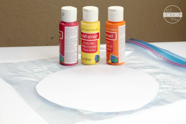 You'll need cardstock, ziplock bags, red/yellow/orange acrylic paint, glue stick, paint brush, and blue paper.