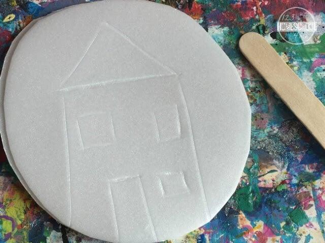 using a craft stick or stick draw design on styrofoam plate
