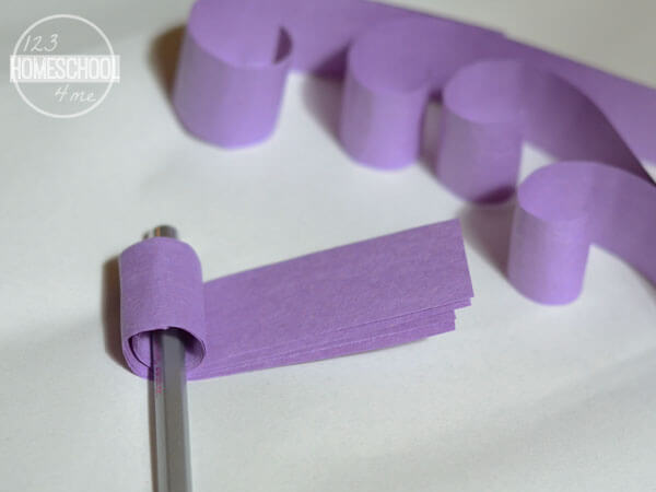 roll construction paper over pencil to curl the strip