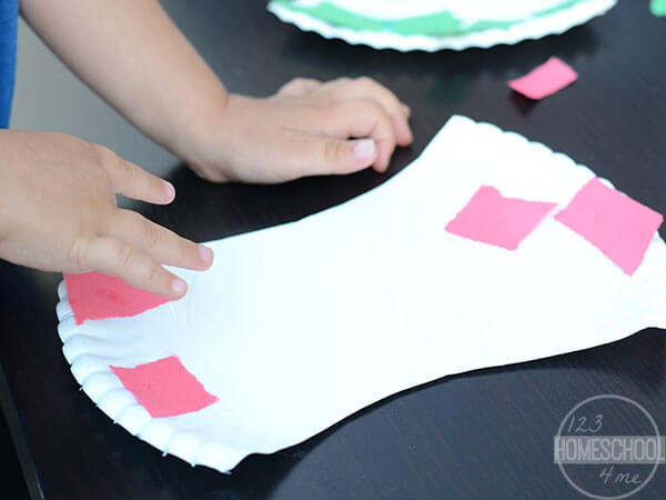 spread glue on paper plate apple core and cover top and bottom with red or green paper