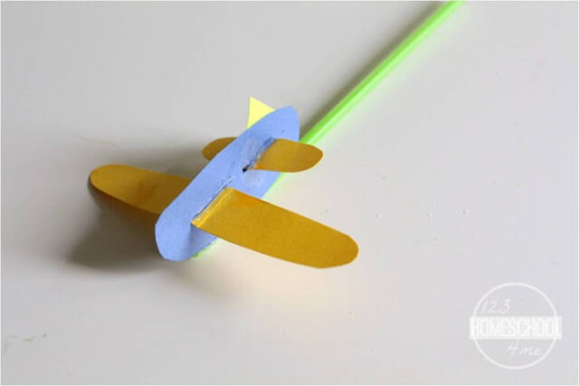 assemble your construction paper pieces into a plane and affix to straw