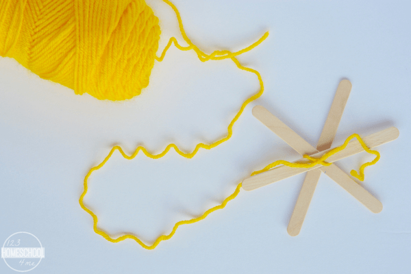 tie yellow yarn around popsicle sticks to make your holiday ornament