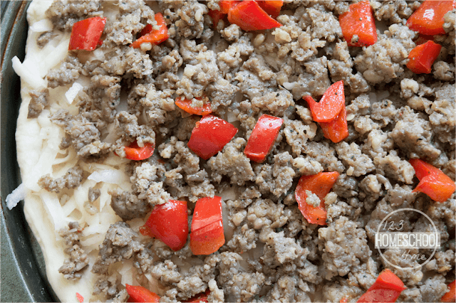 top with thawed, frozen potatoes, cooked ground sausage, and peppers