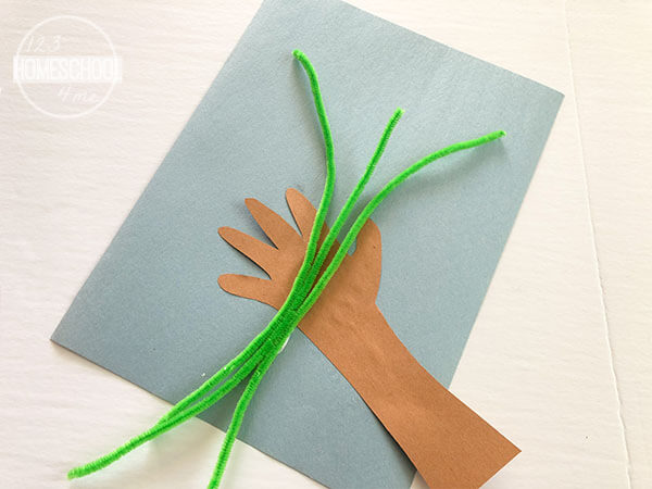 glue handprint on construction paper and glue green pipe cleaners on hand