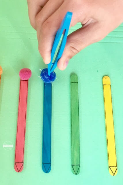 use-tweezers-to-match-pom-pom-color-with-popsicle-stick-color-fine-motor-skills