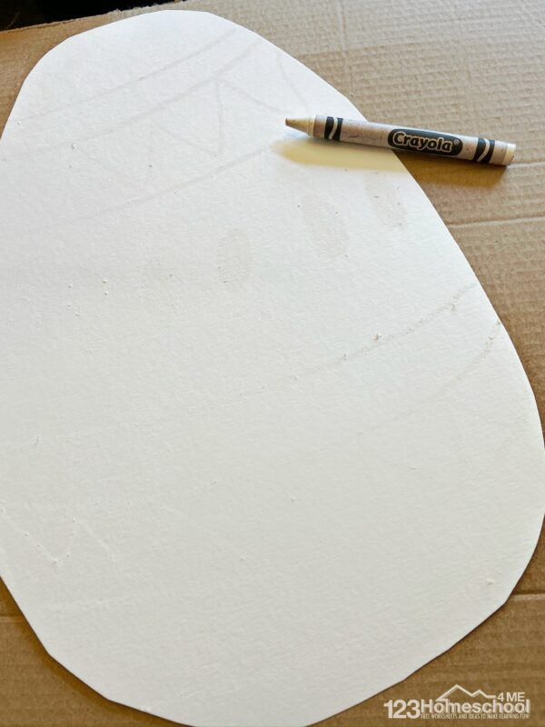make crayon resist drawings using a white crayon on the white egg